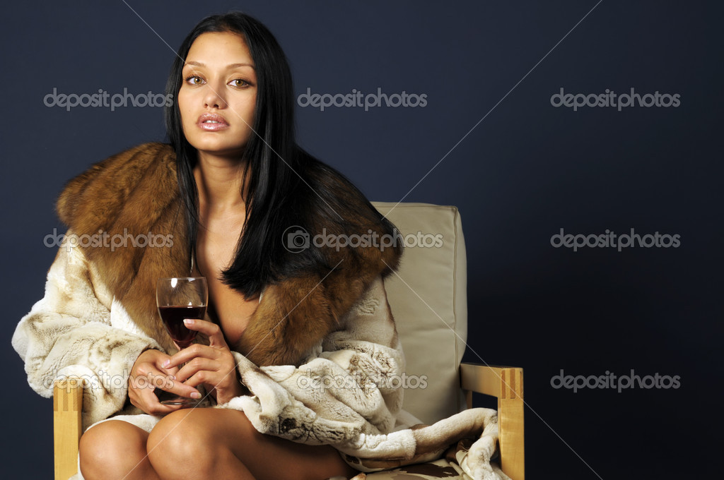 Portrait of the beautiful woman with glass of wine. She dressed in fur coat  Stock Photo #1616676