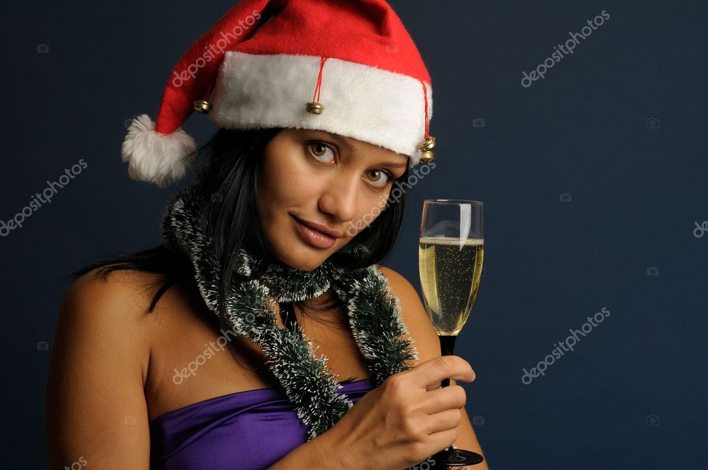 Beautiful exotic woman in the red hat with the glass of champagne into Christmas — Stock Photo #1618050