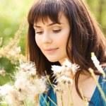 Young beautiful girl among fluffy plants — Stock Photo #1418500
