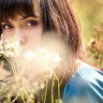 Young beautiful girl among fluffy plants — Stock Photo