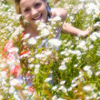 Girl surrounded by flowers — Stock Photo