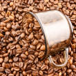 Glass cup of coffee filled up with beans - Stock Photo