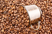 Glass cup of coffee filled up with beans — Stock Photo