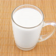 Glass cup of milk on wooden placemat — Stock Photo