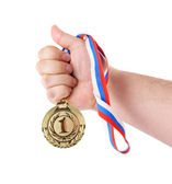 Gold medal in hand isolated on white — Stock Photo