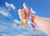Hand holding gold medal — Stock Photo