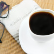 Coffee cup with glasses and newspaper — Stock Photo