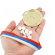 Gold medal and tablets on hand — Stock Photo