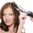 Foto Stock: Curling female brunette hair with roller