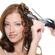 Curling female brunette hair with roller — Stok fotoğraf