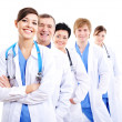 Happy doctors in hospital gowns in row - Stok fotoğraf