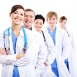 图库照片: Happy doctors in hospital gowns in row