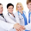 图库照片: Unity of four happy successful doctors