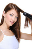 Beautiful girl hairstyle hair iron — Stock Photo