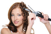 Curling female brunette hair with roller — Stockfoto