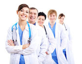 Happy doctors in hospital gowns in row — Stock Photo