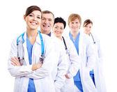 šťastné lékaři v nemocnici šaty v řádku — Stock fotografie