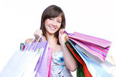 Cheerful girl holding colored bags — Stock Photo