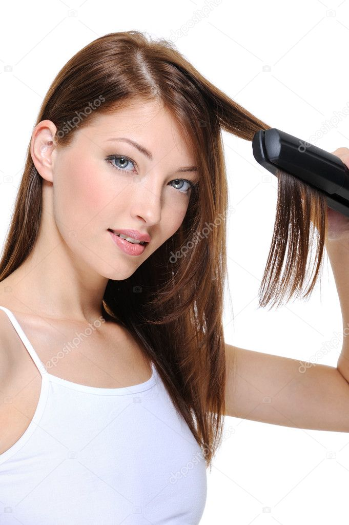 Portrait of young beautiful girl doing hairstyle with hair iron — Stock Photo #1461719