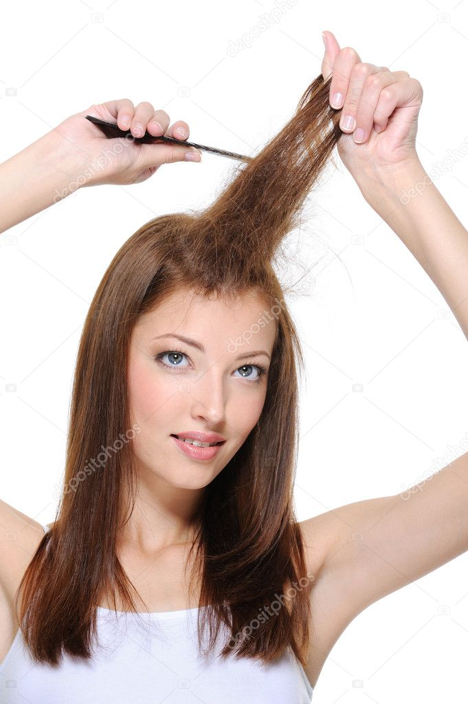 Portrait of young brunette girl doing backcombing with comb — Stock Photo #1461738
