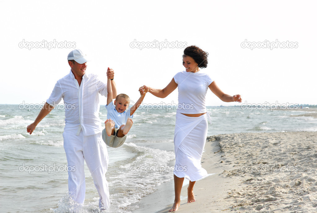 Father and mother playing on beach with little son — Stock Photo #1462114