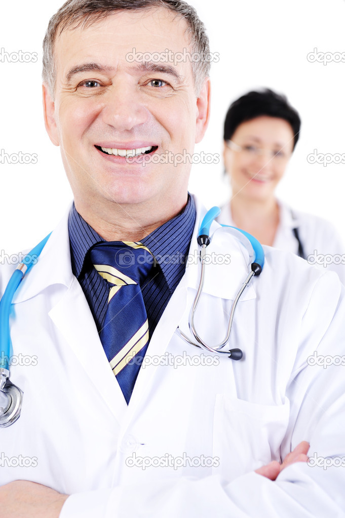 Portrait of happy smiling mature male doctor with  female doctor at  background — Stock Photo #1462799