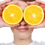 Female face with fresh section orange — Stock Photo