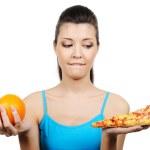 Female choose between pizza and orange — Stock Photo #1477391