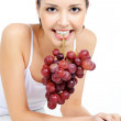 Woman holding a bunch of grapes — Stock Photo