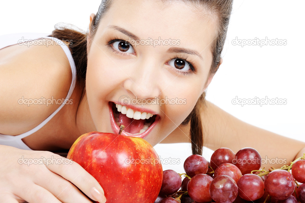 Portrait of expressive attractive young woman with apple and grapes  Stock Photo #1477730