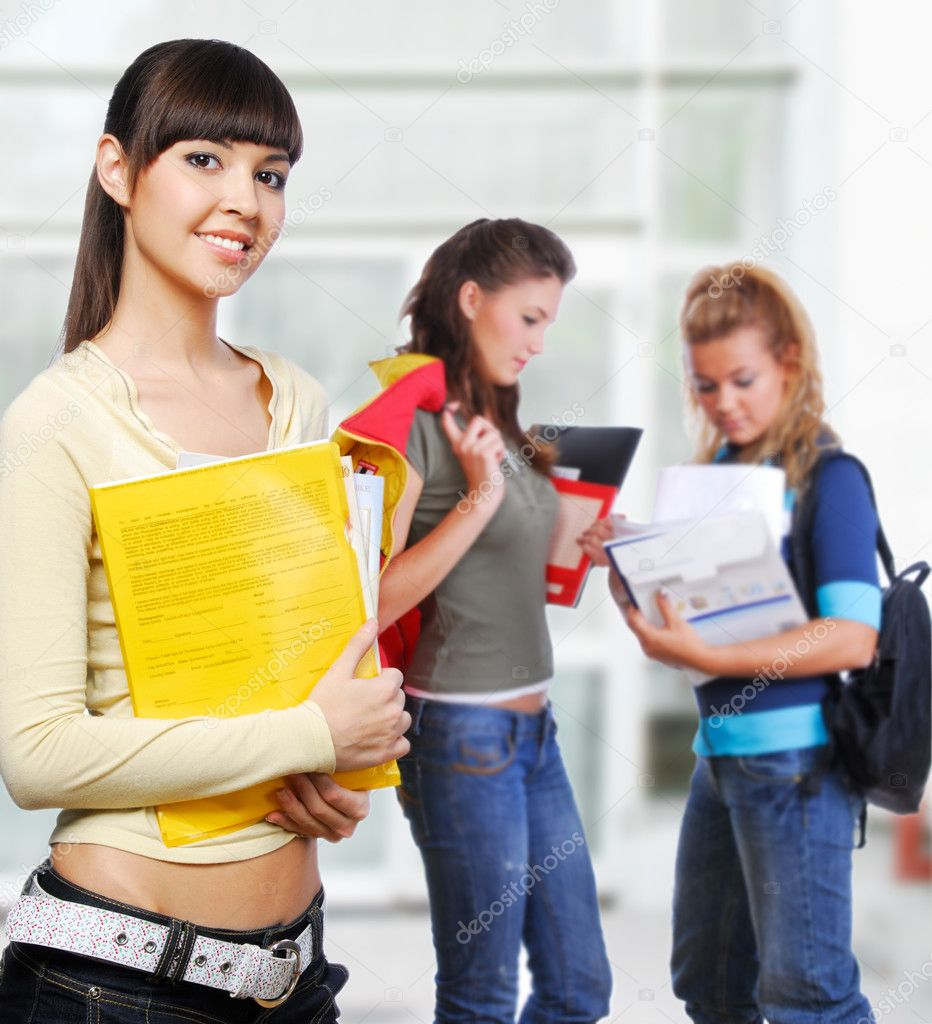 Clever student holding yellow folder in hands - focus on foreground.   Stok fotoraf #1478316