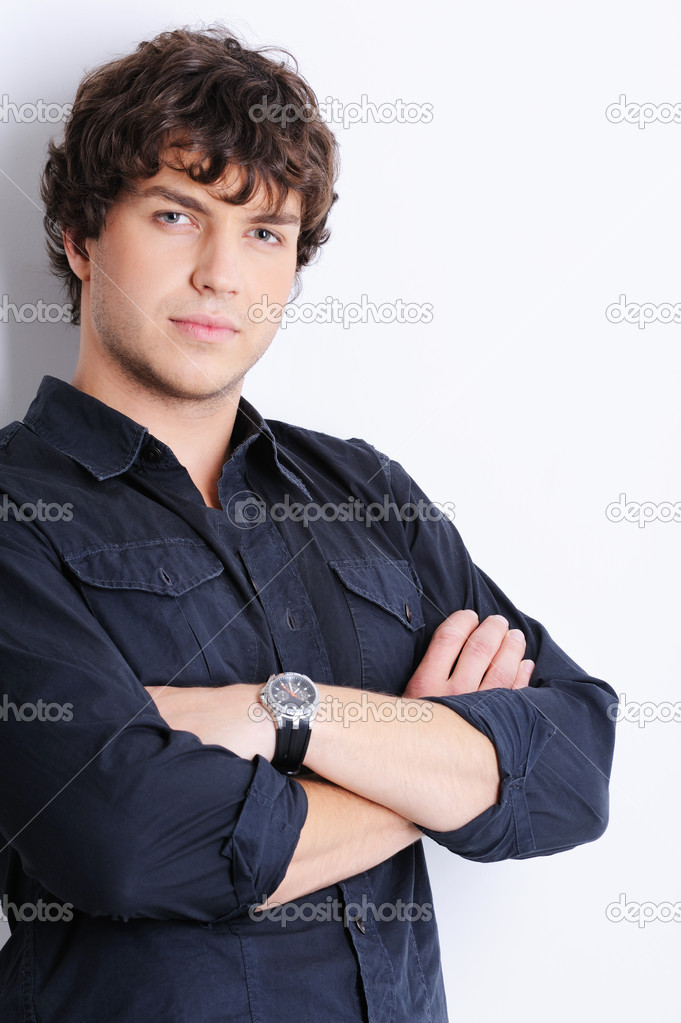 Portrait of a pretty calm young guy posing in the studio  Stock Photo #1485773