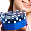 Half smiling face of  female with gift - Stock Photo