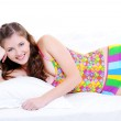 Smiling female lying down on bed — Stock Photo