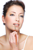 Woman using lip concealer brush — Stock Photo