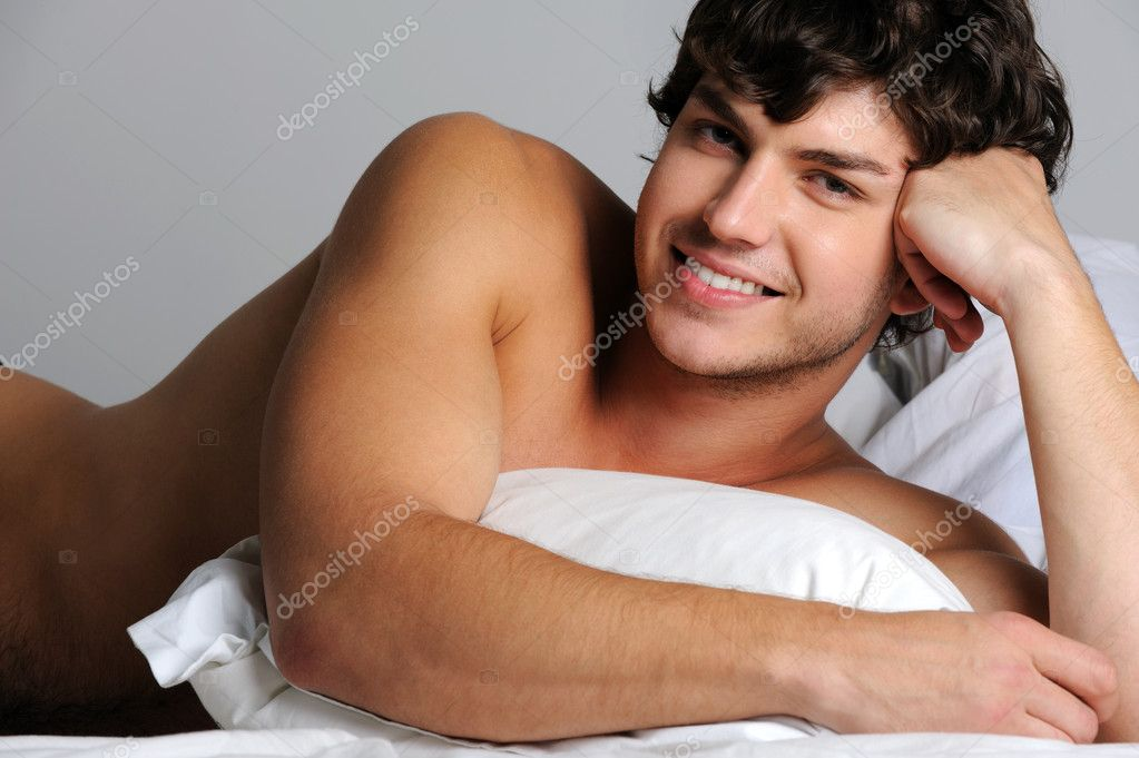 Handsome sexy smiling young man lying in bed with pillow — Stock Photo #1503595