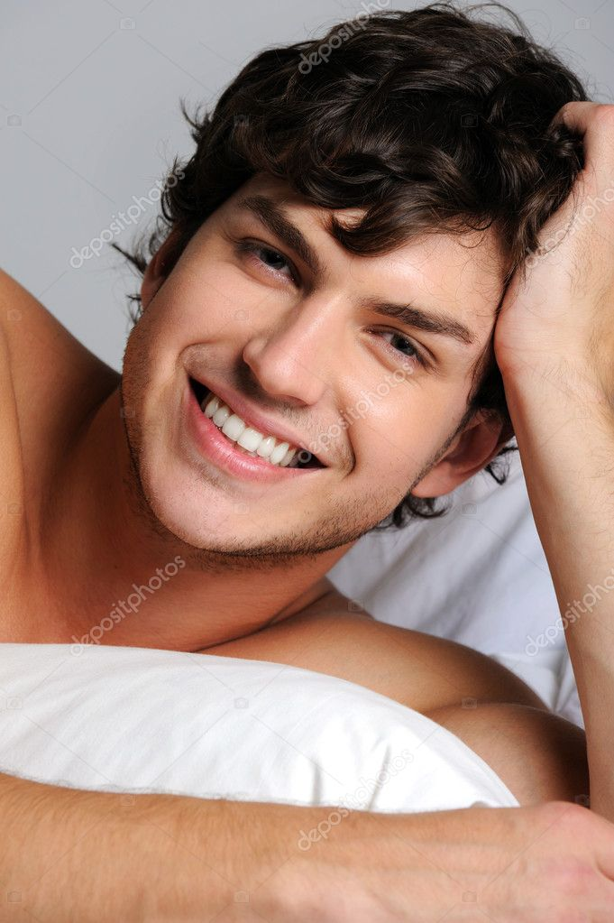 Closeup face of a smiling happy young man lying in bed  Stock Photo #1503605