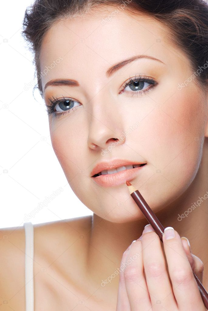 Portrait of beautiful woman applying lipstick using lip concealer brush — Stock Photo #1503761