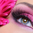 Stock Photo: Woman eye with pink make-up and flower