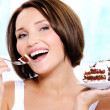 Cute young woman eats a  cake - Stock Photo