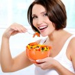 Smiling young woman eats salad — Stock Photo