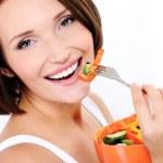 Happy woman eats vegetable salad — Stock Photo