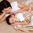 Mum to the sleeping small son - Stock Photo