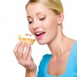 Young woman eats the sweet cake — Stock Photo #1519888