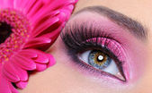 Woman eye with pink make-up and flower — Stock Photo