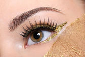 Female eye with golden make — Stock Photo
