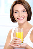 Cheerful woman holding glass of juice — Stock Photo