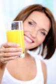 Mujer sostiene un vaso de jugo de naranja — Foto de Stock