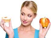 Woman choose from cake and apple — Stock Photo