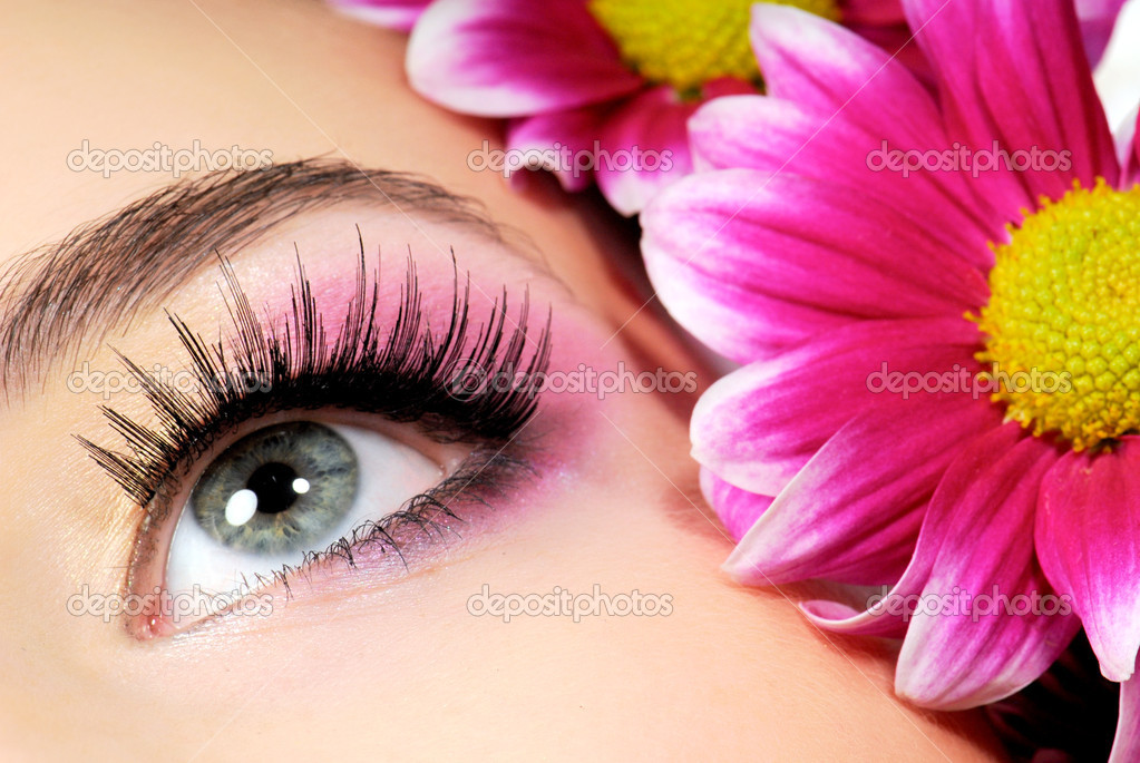 Close-up of woman green eye. Pink flower on background. — Stock Photo #1512826